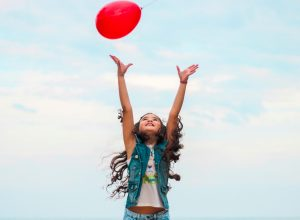 student with red balloon